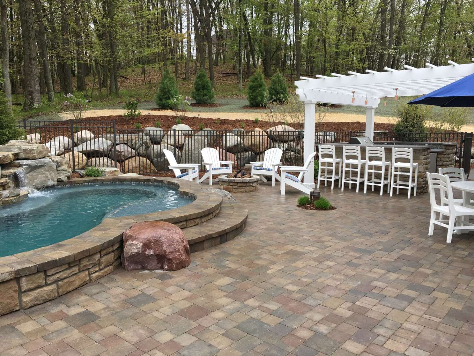 Grand Rapids raised free-form pool, waterfall, outdoor kitchen, and pergola